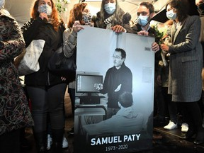 Relatives and colleagues hold a picture of Samuel Paty during the 'Marche Blanche' in Conflans-Sainte-Honorine, northwest of Paris, on Oct. 20, 2020, in solidarity after a teacher was beheaded for showing pupils cartoons of the Prophet Mohammed.