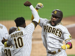 Jurickson Profar congratulates teammate Fernando Tatis Jr. of the San Diego Padres after his two-run home run during Game 2 of the National League Wild Card Series against the St. Louis Cardinals at PETCO Park on October 1, 2020 in San Diego.