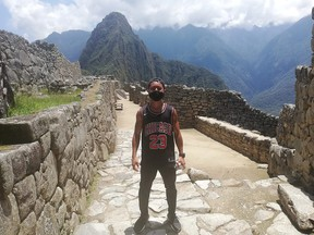 Japanese tourist Jesse Takamaya poses for a photograph during his visit to the ruins of Machu Picchu, Peru October 10, 2020.