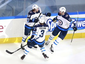 Jansen Harkins (58) of the Winnipeg Jets celebrates his first NHL playoff goal with teammates Tucker Poolman (3) and Adam Lowry (17) in the first period against the Calgary Flames during Game 2 of the Western Conference Qualification Round prior to the 2020 NHL Stanley Cup Playoffs in Edmonton.
