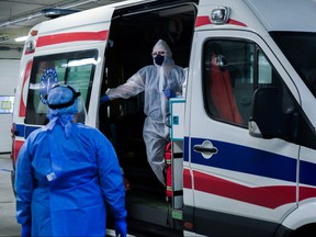 Medical personnel wear protective suits, masks, gloves as they discuss details about a patient who arrived from Warsaw at the SOR of Krakow University Hospital on Nov. 3, 2020 in Krakow, Poland.