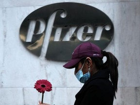 A woman walks by Pfizer's New York headquarters as New York City tries to contain a spike in COVID-19 cases on November 16, 2020 in New York City.