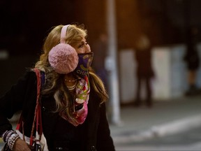 A woman wearing a protective face mask and earmuffs crosses the street during the COVID-19 outbreak, in Beverly Hills, Calif., Nov. 20, 2020.