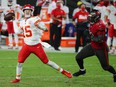 Chiefs quarterback Patrick Mahomes (left) makes a pass as Buccaneers defensive end William Gholston closes in during the first half in Tampa yesterday. Mahomes threw for 462 yards and three TDs in the 27-24 win over the Chiefs.