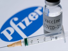 "This illustration picture shows a syringe and a bottle reading ""Covid-19 Vaccine"" next to the Pfizer company logo."