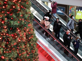 Shoppers wearing mandatory masks pass the Christmas Tree at Toronto's Eaton Centre mall, two days before COVID-19 restrictions are reintroduced to Toronto and Peel regions, Nov. 21, 2020.