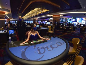 A casino dealer waits at her blackjack table prior to the official opening of the Circa Resort & Casino during a grand opening event in Las Vegas October 27, 2020.