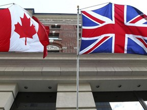 The Canadian flag flies alongside the British flag outside an Ottawa hotel, Sept 26, 2012.
