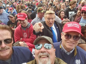 Donald Trump impersonator Donald Rosso (pointing) poses with fans at a 2019 Trump rally in Grand Rapids, Mich.
