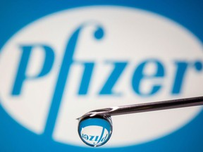 Pfizer's logo is reflected in a drop on a syringe needle in this illustration taken November 9, 2020.