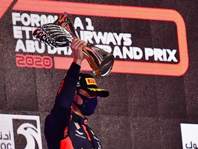 Red Bull's Max Verstappen celebrates winning the Abu Dhabi Grand Prix on the podium in Abu Dhabi, United Arab Emirates, Dec. 13, 2020.