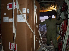 Special freezers for COVID-19 vaccines are unloaded by MCpl Julien Simard members of the Royal Canadian Air Force's 436 Transport Squadron in support of the Public Health Agency of Canada from a transport aircraft in an unidentified northern territory, Canada Dec. 12, 2020.
