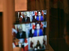 Canadian Prime Minister Justin Trudeau and UK Prime Minister Boris Johnson are seen in a pre-recorded video during a news conference in Ottawa, Saturday, Nov. 21, 2020.