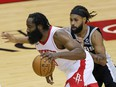 James Harden of the Houston Rockets drives past Patty Mills of the San Antonio Spurs at the Toyota Center on December 17, 2020 in Houston.