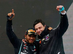 Mercedes' Lewis Hamilton celebrates on the podium with team principle Toto Wolff after winning the race and the world championship.