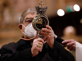 Archbishop Cardinal Crescenzio Sepe holds a vial containing the blood of San Gennaro in Naples, Italy, December 16, 2020.