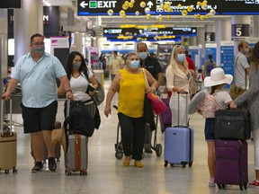 Travellers wearing protective face masks walking through Concourse D at the Miami International Airport on Sunday, Nov. 22, 2020, in Miami, Fla.