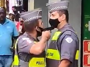 Police officer Felipe do Nascimento, left, points his gun at fellow officer Marcio Simao in a screengrab captured from video in Sao Paulo, Brazil, on Friday, Dec. 4, 2020.