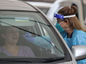 A medical worker swabs a member of the public at the Bondi Beach drive-through coronavirus disease (COVID-19) testing centre as the city experiences an outbreak in Sydney, Australia, December 21, 2020.