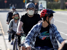 Masked cyclists are seen in Golden Gate Park ahead of the new stay-at-home order in attempts to stem coronavirus spikes in San Francisco, Sunday, Dec. 6, 2020.