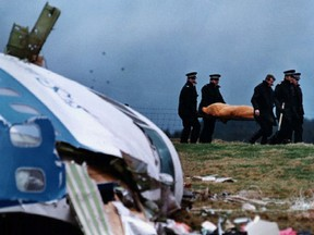 File photo from December 22, 1988 shows rescue personnel carrying a body away from the site of the crash in Lockerbie.