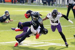 Running back Derrick Henry #22 of the Tennessee Titans attempts to break a tackle from linebacker L.J. Fort #58 of the Baltimore Ravens during the fourth quarter of their AFC Wild Card Playoff game at Nissan Stadium on January 10, 2021 in Nashville, Tennessee.