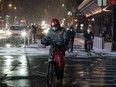 A delivery person wearing a protective mask rides his bike as snow begins to fall in Times Square during a snow storm, during the pandemic in the Manhattan borough of New York City, U.S., Jan. 31, 2021.