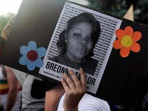 A demonstrator holds a sign with the image of Breonna Taylor, a black woman who was fatally shot by Louisville police officers, during a protest against the death of George Floyd in Minneapolis, in Denver, on June 3, 2020.