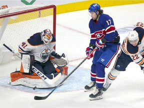 Montreal Canadiens winger Josh Anderson deflects the puck in front of Edmonton Oilers goalie Mike Smith behind defenceman Tyson Barrie during third period in Montreal on Feb. 11, 2021.