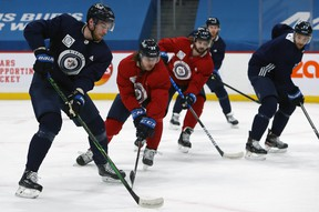 Pierre-Luc Dubois (left) looks to get a pass through to Trevor Lewis (right) during Jets practice on Monday.