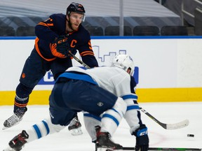 Edmonton Oilers' Connor McDavid (97) passes past Winnipeg Jets' Neal Pionk (4) during first period NHL action at Rogers Place in Edmonton, on Monday, Feb. 15, 2021.