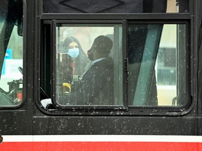 People wearing protective masks board a city transit bus during the COVID-19 pandemic in Toronto, Feb. 19, 2021.