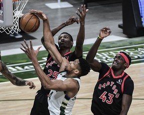 Bucks' Giannis Antetokounmpo (middle) reaches for a rebound under pressure from Raptors' Chris Boucher (25) and Pascal Siakam during the first quarter at Fiserv Forum in Milwaukee on Tuesday, Feb. 16, 2021.