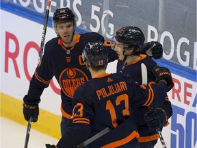 Edmonton Oilers Ryan Nugent-Hopkins (93) celebrates his goal against the Calgary Flames with teammates Connor McDavid (97) and Jesse Puljujarvi (13) during first period NHL action on Saturday, Feb. 20, 2021 in Edmonton.