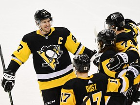 Sidney Crosby of the Pittsburgh Penguins and his teammates celebrate a goal against the New York Islanders at PPG PAINTS Arena on February 20, 2021 in Pittsburgh.