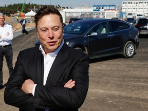 In this file photo, Tesla CEO Elon Musk talks to media as he arrives to visit the construction site of the future U.S. electric car giant Tesla in Gruenheide near Berlin on Sept. 3, 2020.