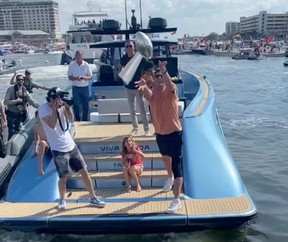 Tampa Bay Buccaneers quarterback Tom Brady throws the Lombardi trophy during a boat parade celebrating the team's Super Bowl victory February 10, 2021 in Tampa.