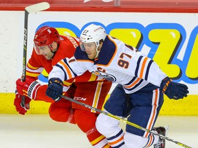 The Calgary Flames' Mark Giordano is in a foot race with the Edmonton Oilers' Connor McDavid at the Saddledome in Calgary on Friday, Feb. 19, 2021.
