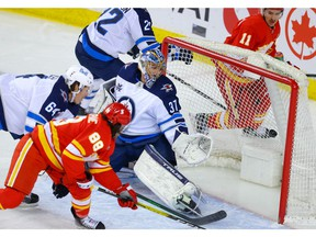 Calgary Flames forward Andrew Mangiapane scores a goal against Connor Hellebuyck of the Winnipeg Jets during NHL hockey in Calgary late Tuesday night.