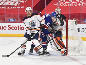 Evan Bouchard (75) of the Edmonton Oilers and Joel Armia (40) of the Montreal Canadiens battle for position in front of Oilers goaltender Mike Smith (41) at the Bell Centre on Feb. 11, 2021, in Montreal.