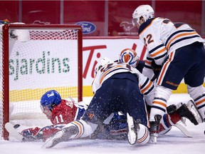 Montreal Canadiens right wing Brendan Gallagher (11) crashes into the net after diving across Edmonton Oilers goaltender Mikko Koskinen (19) to score the Canadiens third goal during NHL action in Montreal on Tuesday, March 30, 2021.