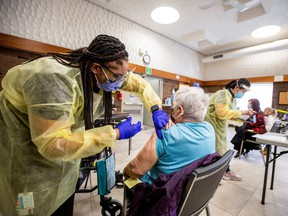 Nurse Tahani McDonald from Humber River Hospital administers the Moderna COVID-19 vaccine at a Toronto Community Housing seniors building in the northwest end of Toronto, March 25, 2021.