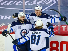 Winnipeg Jets defenceman Logan Stanley (64) celebrates his goal against the Calgary Flames during the second period at Scotiabank Saddledome in Calgary on Saturday, March 27, 2021.