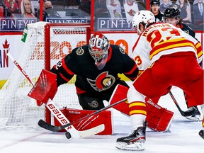 Ottawa Senators goaltender Filip Gustavsson makes a save against Calgary Flames centre Sean Monahan during second-period action at the Canadian Tire Centre.