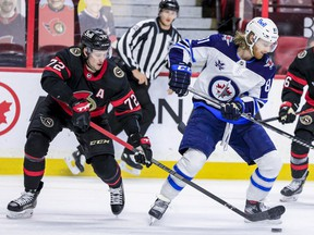 Ottawa Senators defenceman Thomas Chabot (left) checks Winnipeg Jets left wing Kyle Connor during second period NHL action at the Canadian Tire Centre.