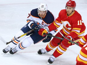 Calgary Flames forward Mikael Backlund and Edmonton Oilers captain Connor McDavid jostle for position at the Scotiabank Saddledome in Calgary on Saturday, April 10, 2021.