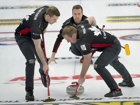 Canada skip Brendan Bottcher delivers his stone as second Brad Thiessen (left) and lead Karrick Martin (right) brush during Draw 4 against Denmark.