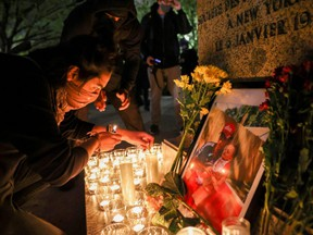 A person lights a candle during a vigil following the fatal police shooting of 20-year-old Black man Daunte Wright in Minnesota, in Washington, D.C., Monday, April 12, 2021.