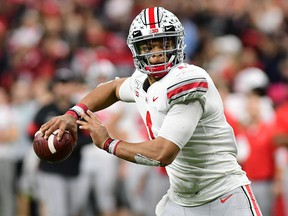 Ohio State quarterback Justin Fields (1) rolls out of the pocket to throw against the Wisconsin Badgers in the 2019 Big Ten Championship Game at Lucas Oil Stadium.