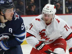 Winnipeg Jets centre Mark Scheifele (left) surveys his passing options with Carolina Hurricanes centre Lucas Wallmark defending in Winnipeg on Tues., Dec. 17, 2019.